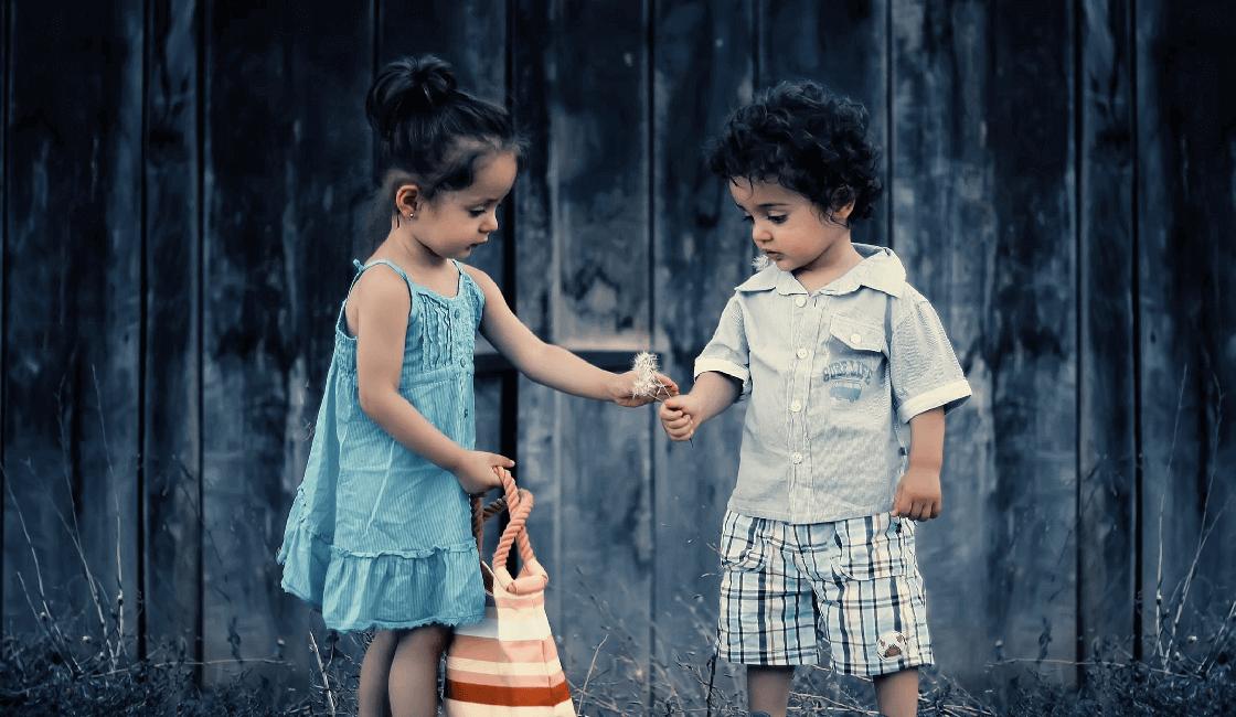 Niña con bolso recibiendo flores de un niño