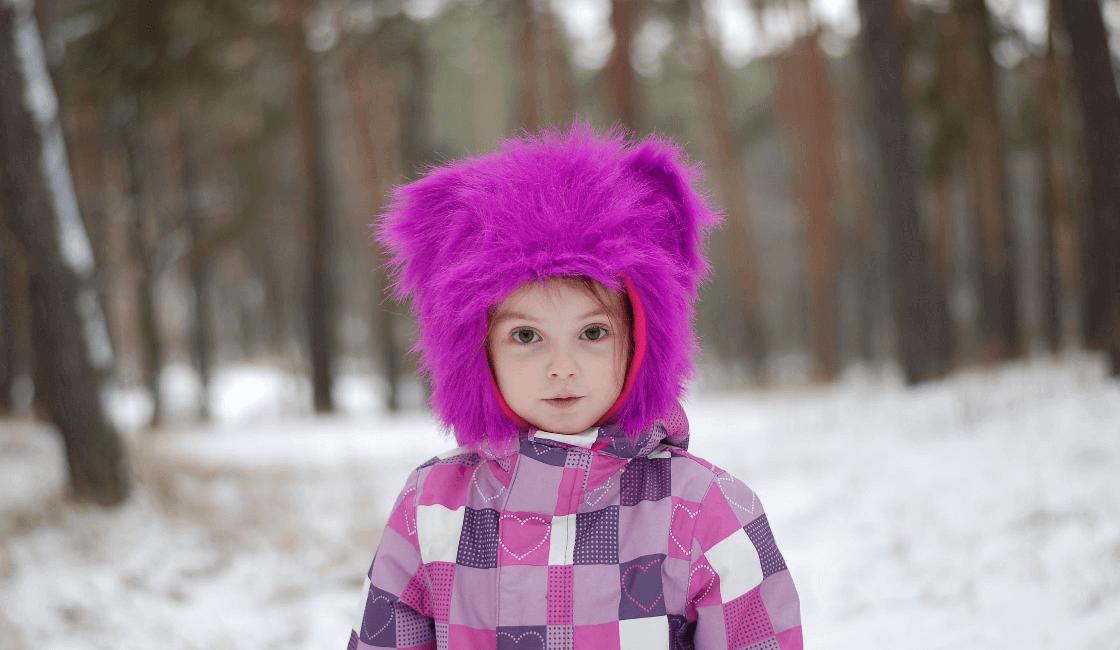 Niña con capucha morada y abrigo a cuadros