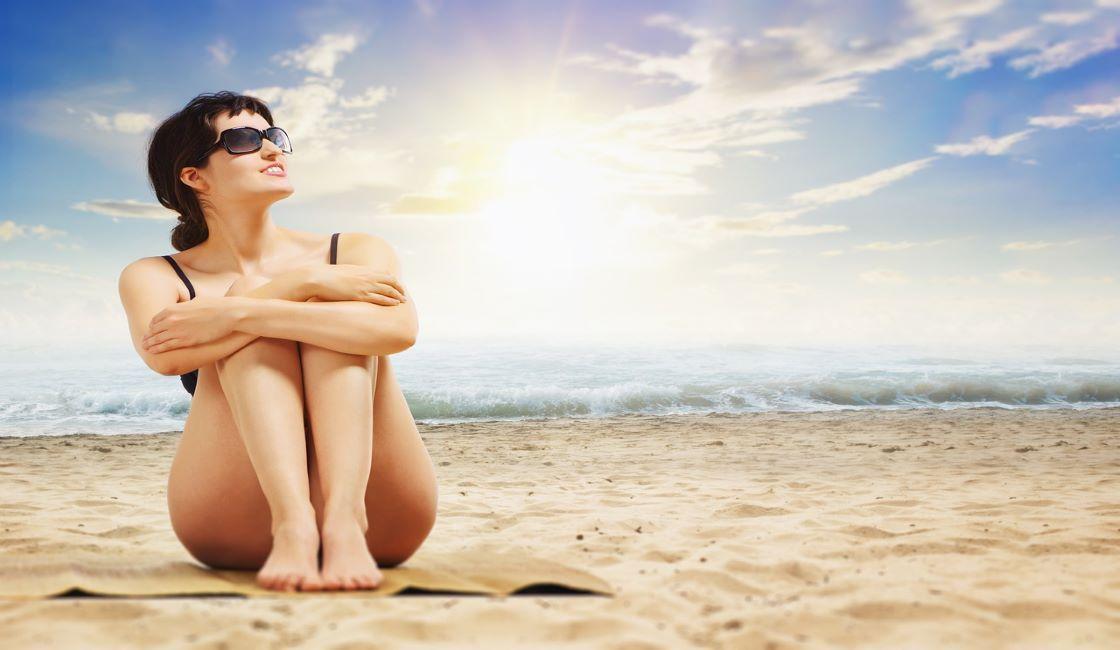 mujer en la playa con los brazos cruzados traje de baño