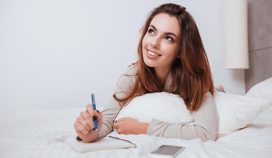 mujer en la cama escribiendseñales de una mujer
