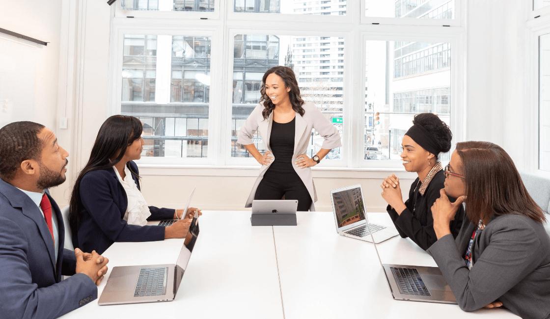 Mujer que lidera un equipo de trabajo en oficina