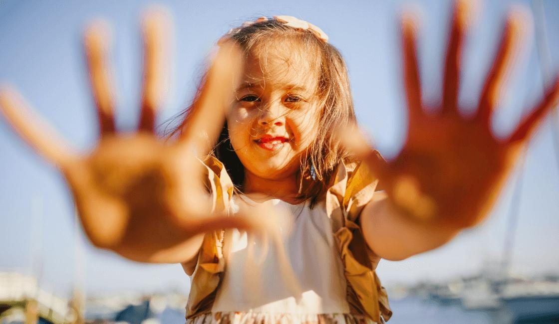 niña feliz con manos