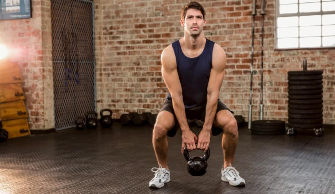hombre entrenando con pesa rusa