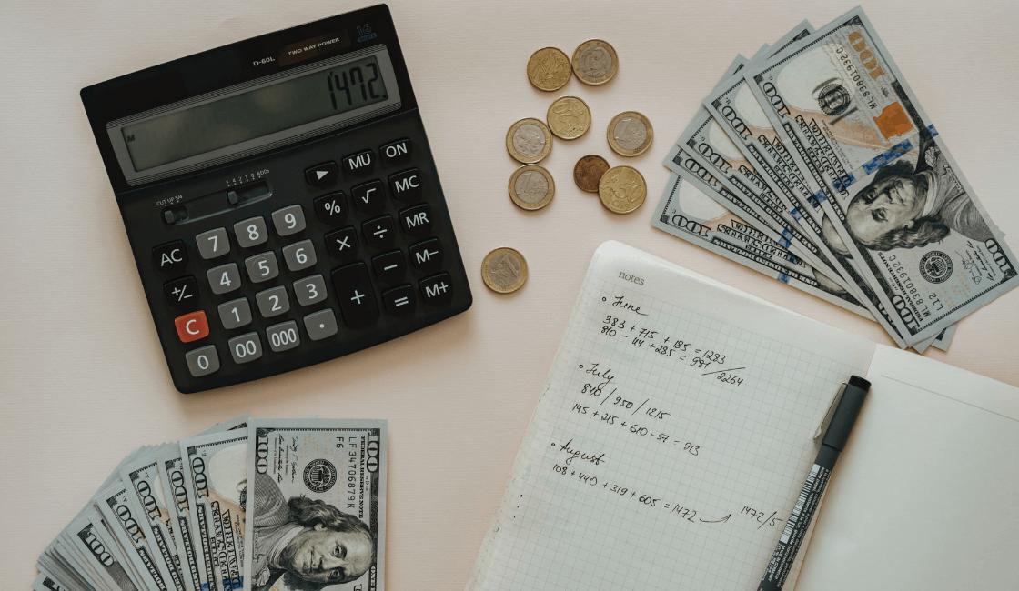 agenda con calculadora y dinero en una mesa