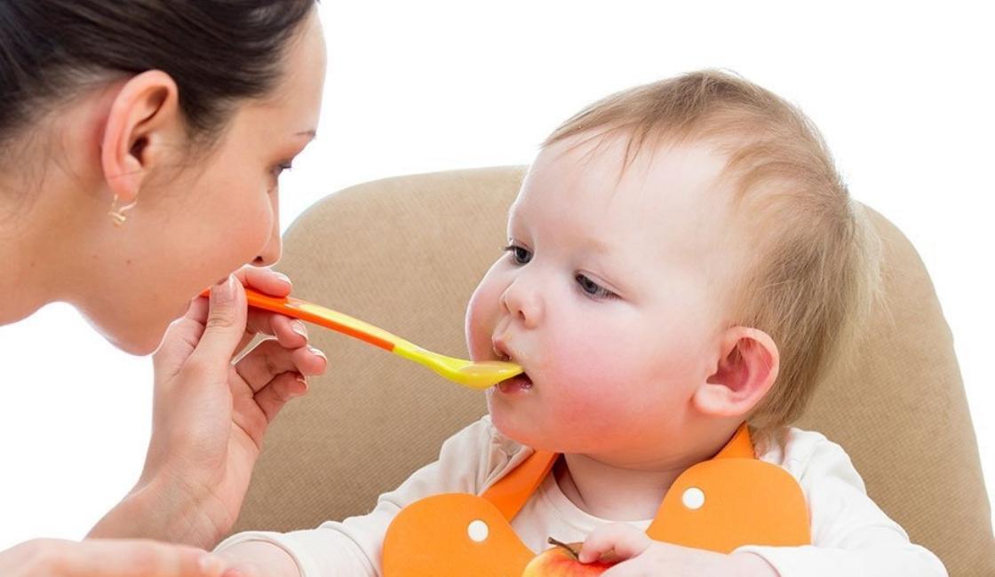 Madre alimenta a su bebe con alimentos ricos en hierro para bebes