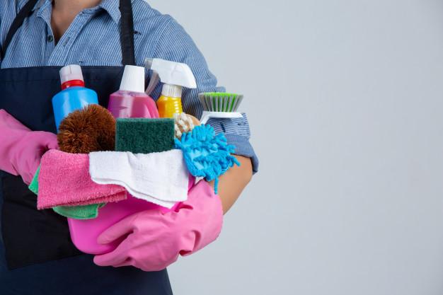 Persona con un balde de artículos de limpieza