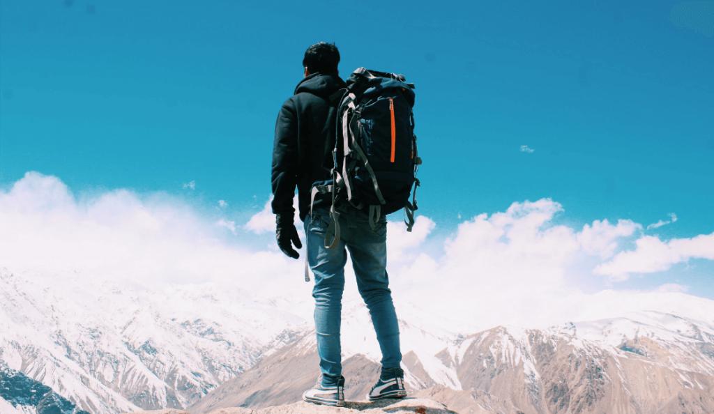 Hombre con mochila sobre montaña nevada